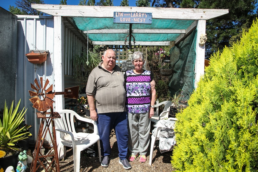 Larry and Lyn Fox standing beneath an awning with the sign - Lyn and Larry's Love Nest.