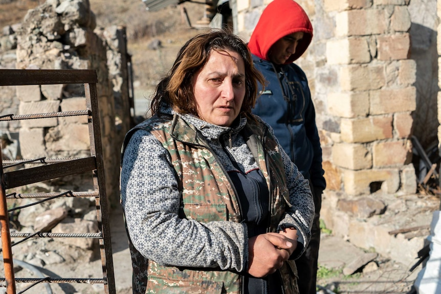 A woman with a worried expression stands in a destroyed building