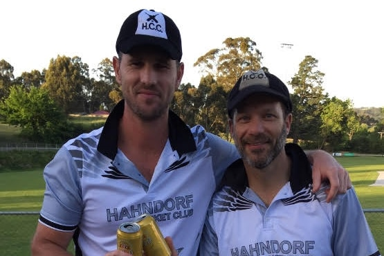 Shaun Tait and Greg Hassold hold a can of beer each and cheers.