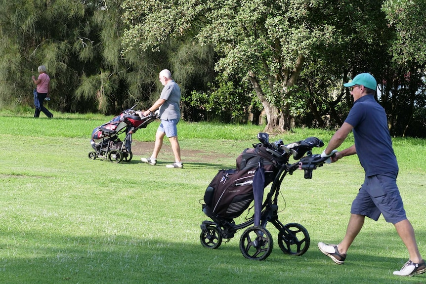 Two golfers and a walker practice social distancing at Marrickville Golf Course, April, 2020.
