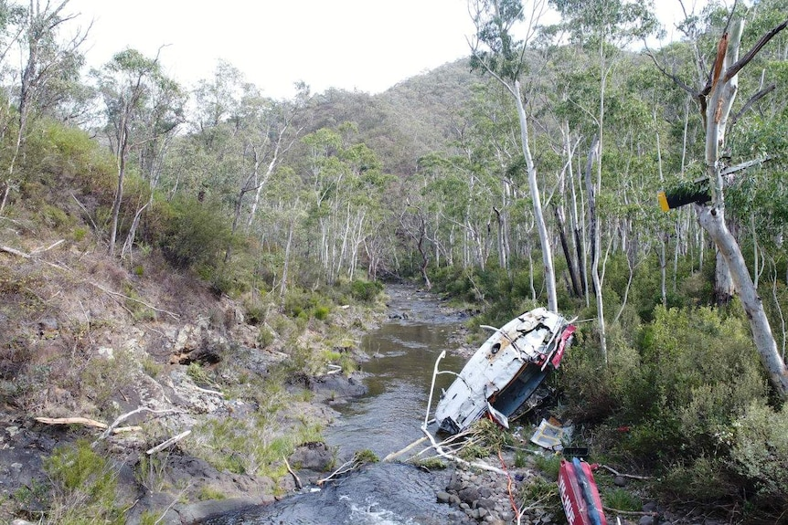 A damaged helicopter lies in a riverbed in a national park.