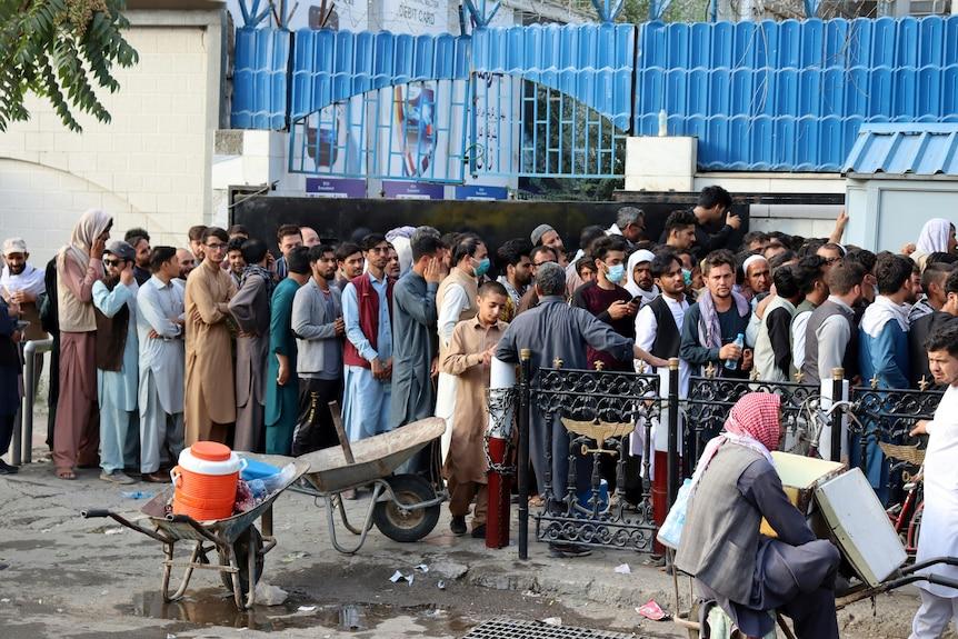A long line of men outside a Kabul building