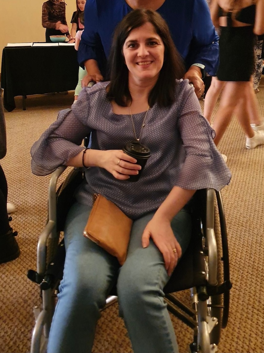 Woman with dark hair smiling, sitting in wheelchair