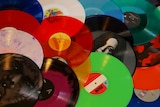 A collection of coloured vinyl records laid out on a table