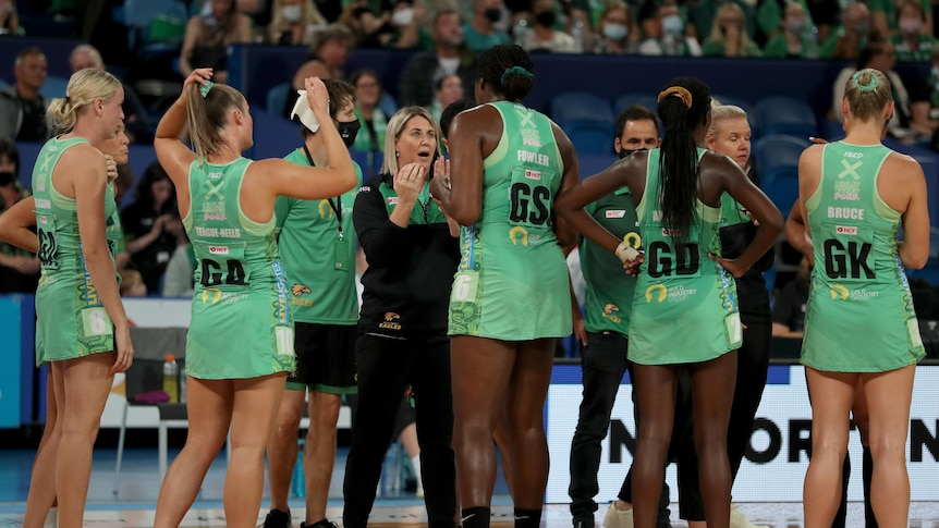 West Coast Fever coach Stacey Marinkovich chats to players in a huddle with green dresses on.