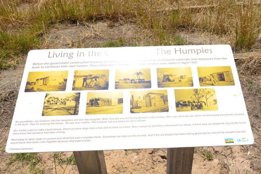 A sign in the bush featuring historical black and white photos and descriptions of life on the reserve