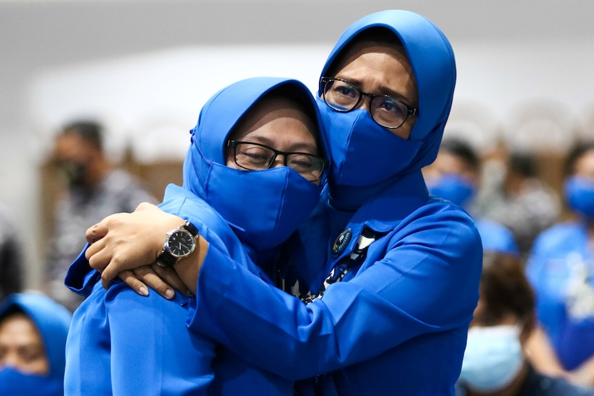 Two women in blue face masks and veils cry while hugging each other