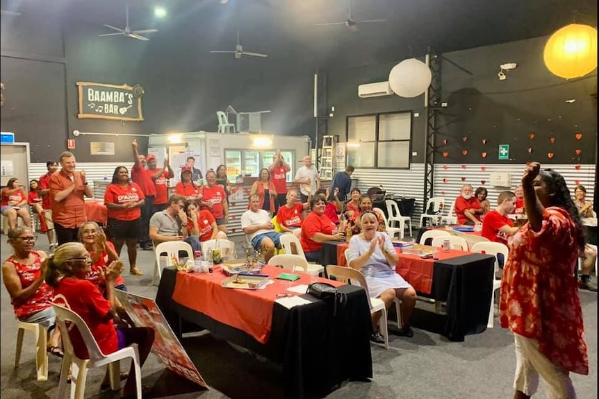 A crowd of people wearing red labor shirts celebrate in a large room.