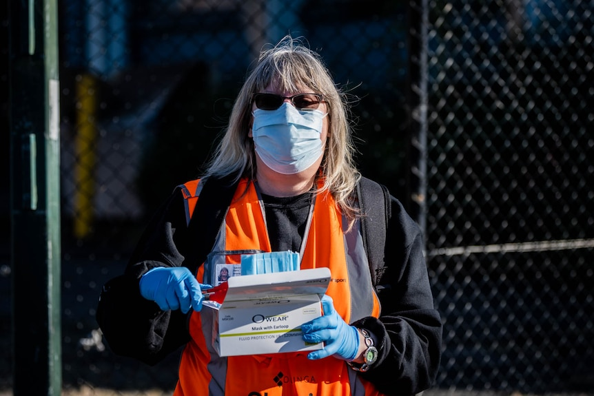 Woman handing out masks