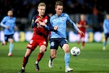 An Adelaide United A-League player and and a Sydney FC opponent contest for the ball.