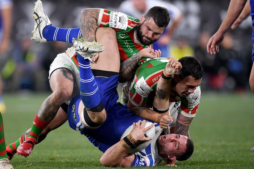 Rugby League player tackling an opposition player during a match.