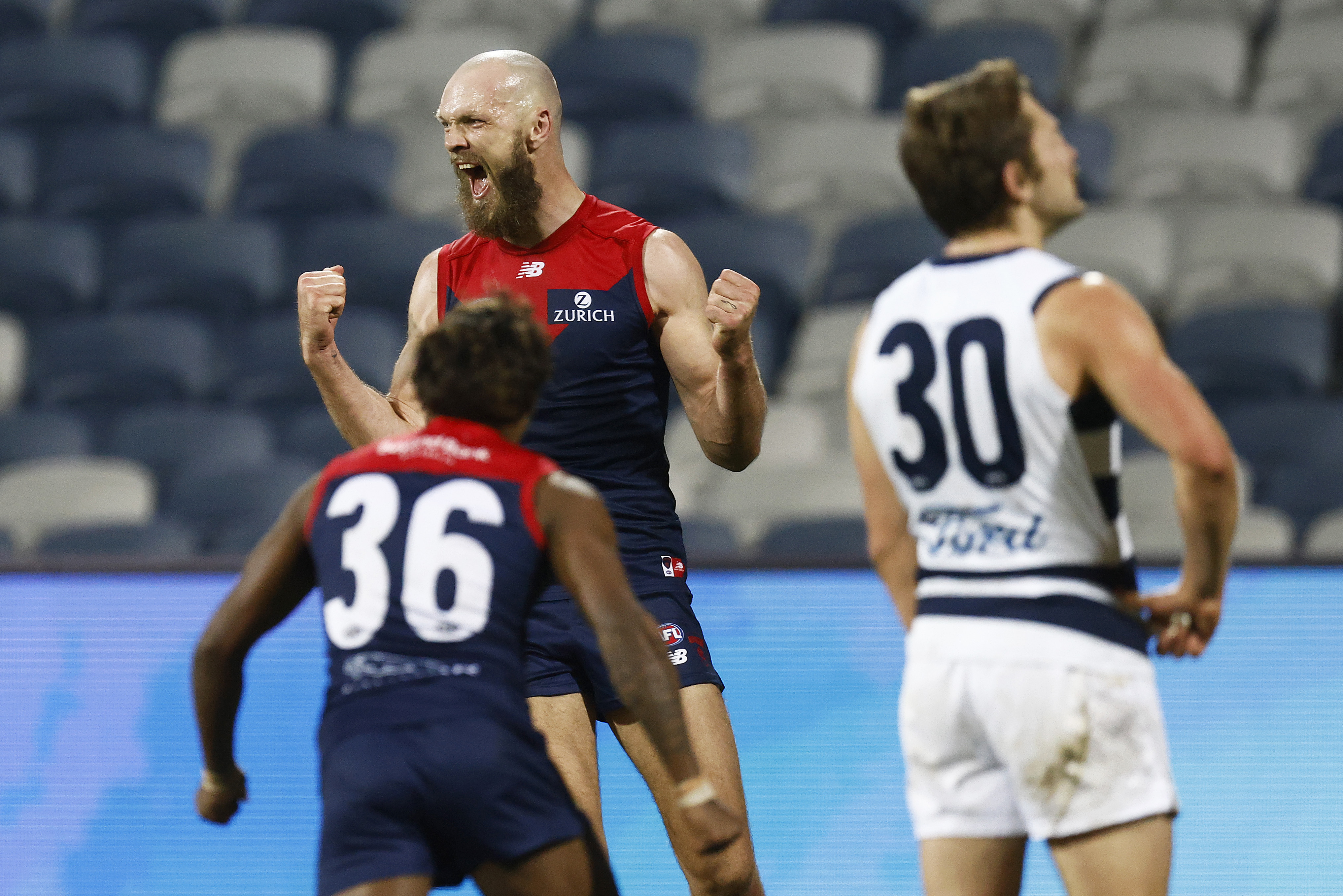A bald, bearded Melbourne AFL player punches the air with his fists and roars in delight as a teammate runs toward him.