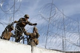 Two Marines hold another as he erects a barbed-wire fence above a concrete barricade.
