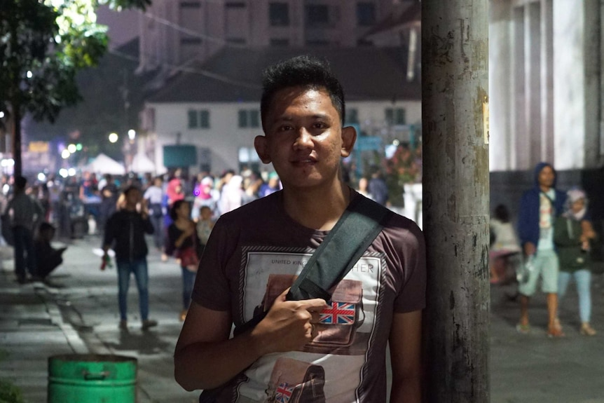"""""""Rangga"""" poses for a photo on a street while leaning against a pole."""