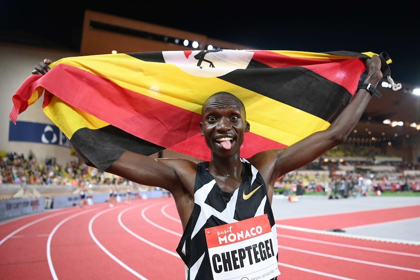 Uganda's Joshua Cheptegei sticks his tongue out as he holds up the Ugandan flag over his head after finishing his race
