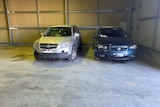 A silver four-wheel-drive and a blue sedan are pictured inside a garage. Each has minor damage.