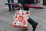 A shopper carries a reusable plastic bag from a Coles store in Sydney.