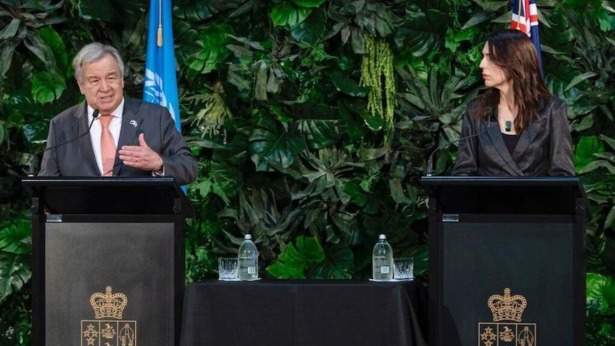 Antonio Guterres stands on a podium next to Jacinda Ardern.