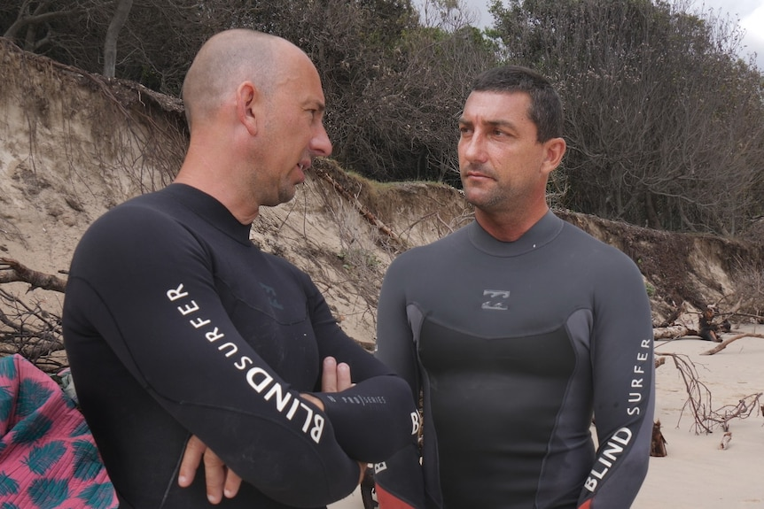 Two men in black wetsuits with 'blind surfer' in white print talking on the beach with sand dunes behind