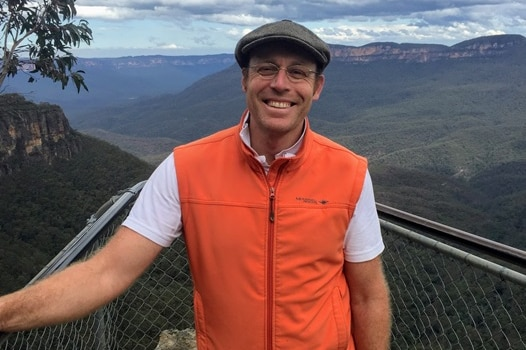 Ian Randall stands in front of a valley wearing an orange Gillet and grey flat cap