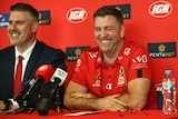 Trevor Gleeson smiles at a press conference, sitting at a table with microphones wearing a red shirt.