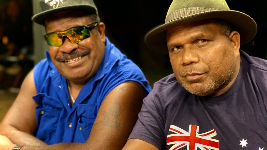 Two men from the Solomon Islands sitting side by side, smiling.