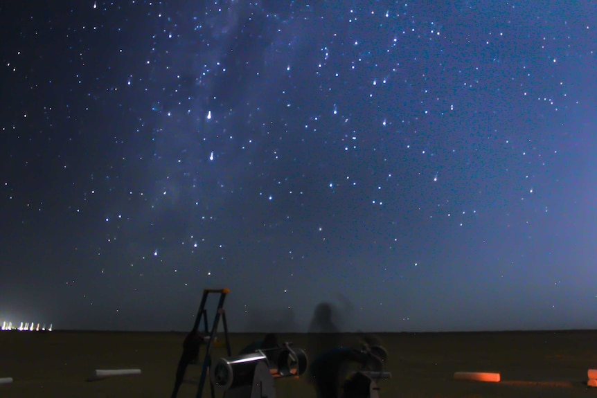 A blue star-filled sky with a ladder and telescopes in the foreground.