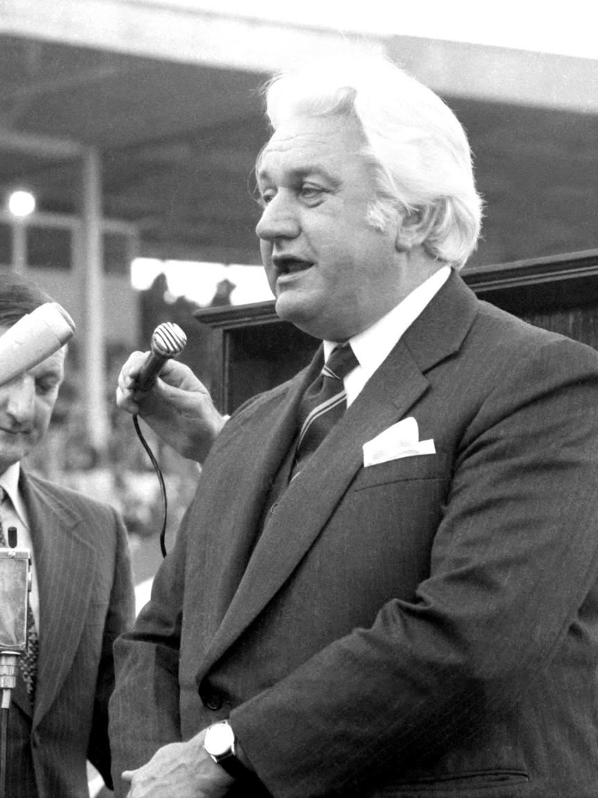 Sir John Kerr speaks in front of a microphone in the middle of the SCG during the 1974 NSWRL Grand Final.