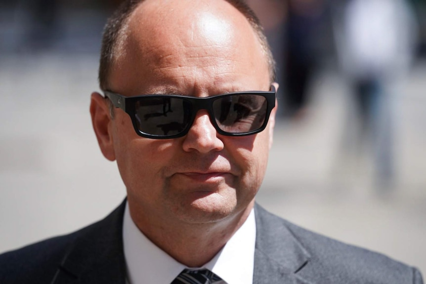 A headshot of Barry Urban wearing a suit and black sunglasses.