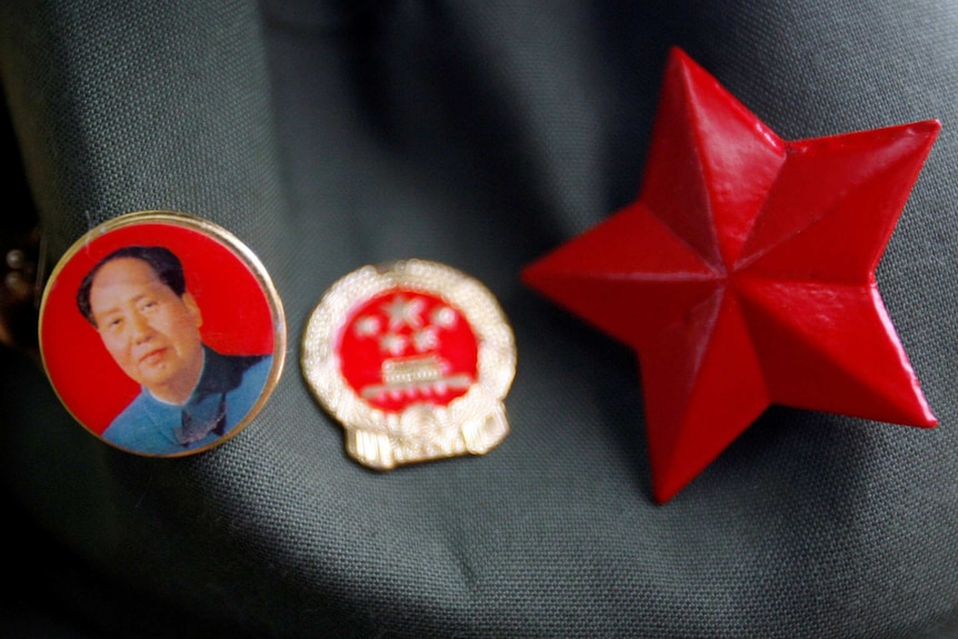 A badge bearing the portrait of Mao Zedong can be seen next to a Chinese Communist Party badge and a red star.