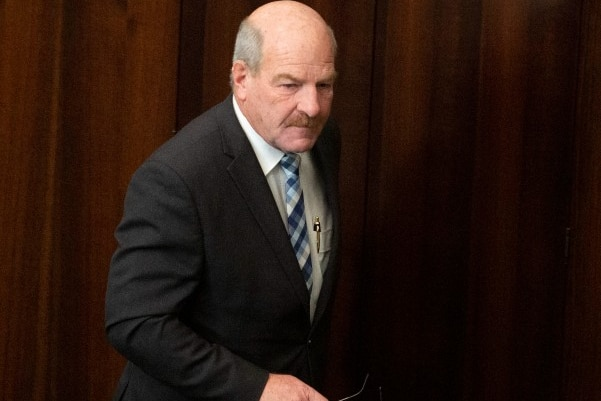 A balding man walks in front of a wooden wall