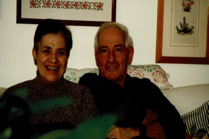 An elderly couple seated on a couch with the woman laughing and the man smiling.