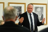 A crowd of heads is visible in front of a gesturing Barnaby Joyce, with a wall of Nationals leaders photos behind him