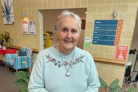 A woman wearing a blue jumper and a silver neckalce