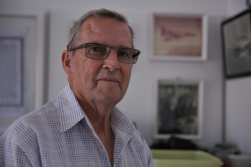 An elderly man with glasses on looking at the camera