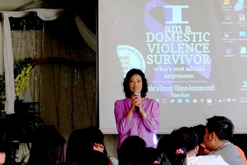 """A woman holding a microphone in front of a presentation that reads """"I am a domestic violence survivor"""""""