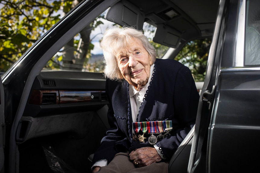 An elderly woman sitting in a car wearing several war medals.