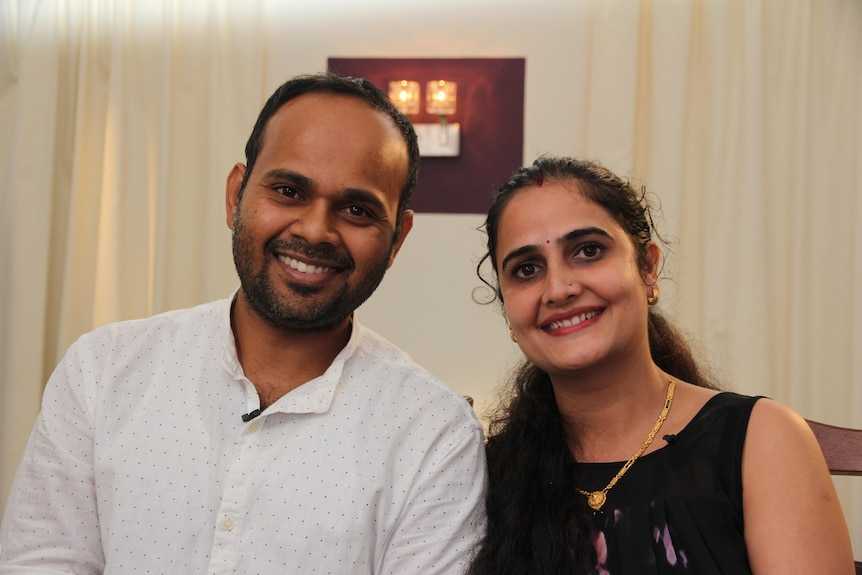 Indian husband and wife smiling at the camera.