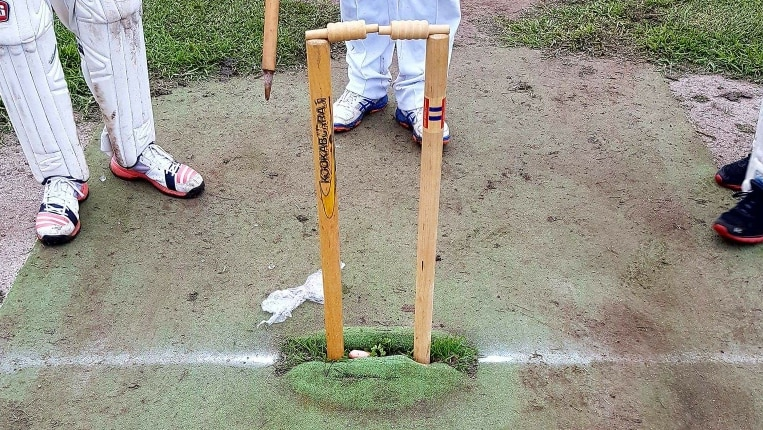 A cricket wicket with leg stump, off stump and bails in place, while a person in cricket whites holds the other stump.
