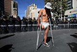 A demonstrator with a physical disability stands in front a riot police barricade.