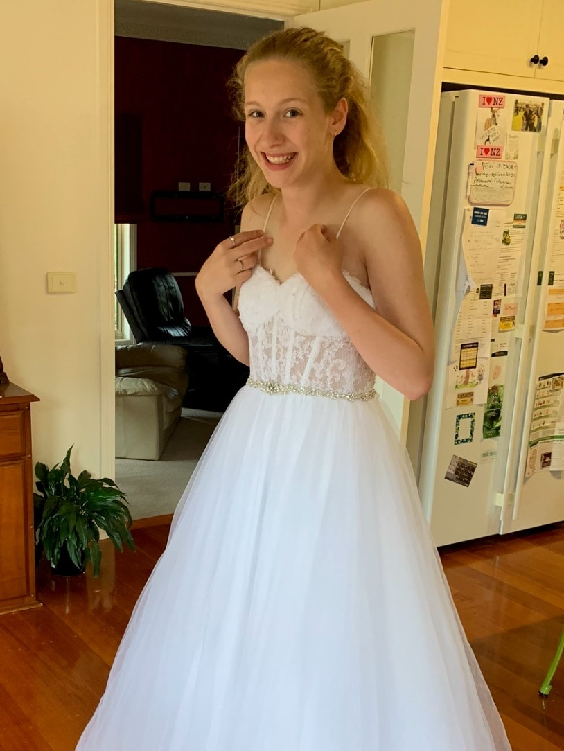 A teenage girl with long blonde hair wearing a white lace dress at home in a kitchen