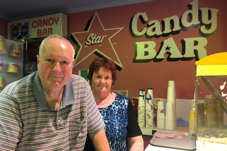 An elderly man and woman stand next to a popcorn machine in a movie theatre candy bar.