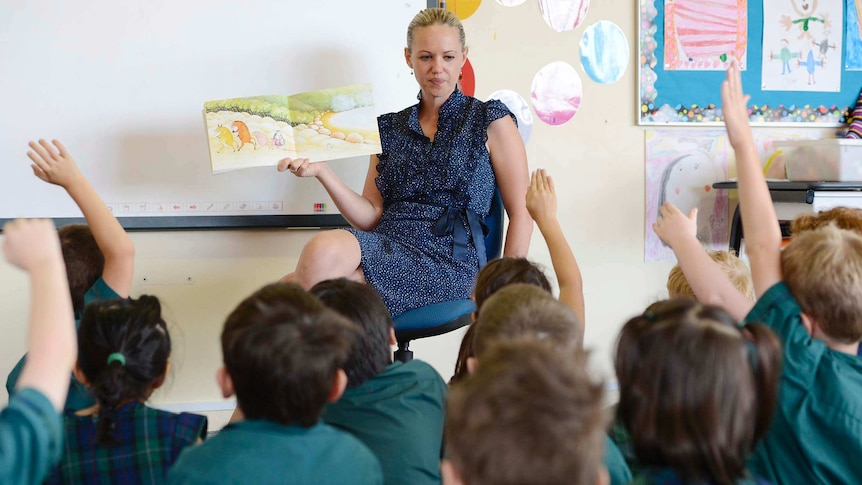 A female teacher holding a picture book open in front of students  who are sitting on the floor in front of her.