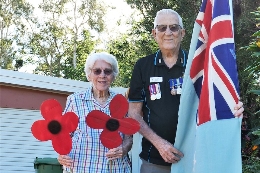 Roy Hartman and his wife Dawn stand in their driveway with a flag and paper poppy flowers.