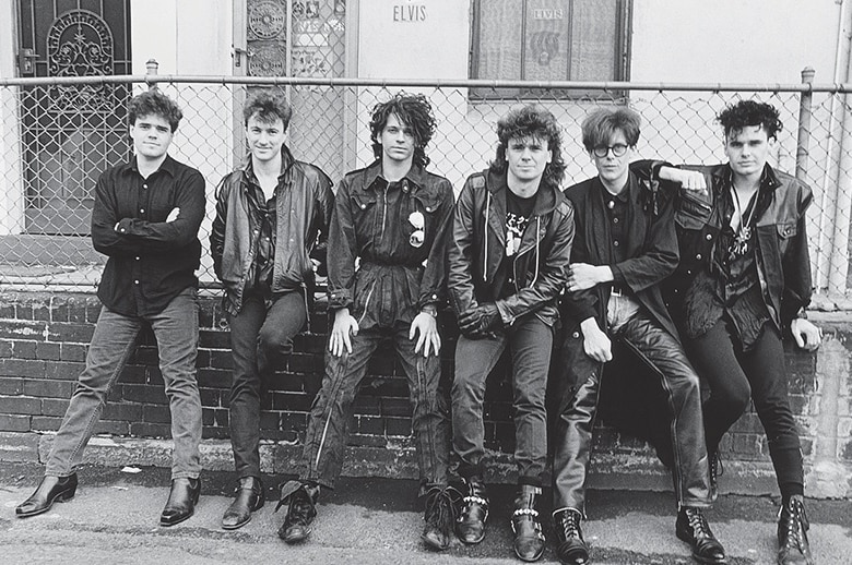A black and white photo of a rock and roll band, dressed in leather.