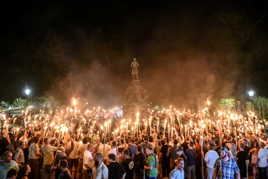 A group of white men with lit tiki torches surrounding a statue of Robert E Lee
