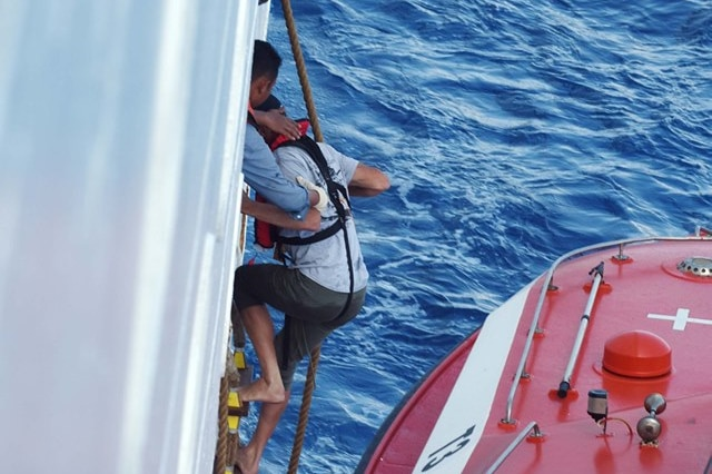 One man is climbing up a ladder on the side of a ship from a rescue boat