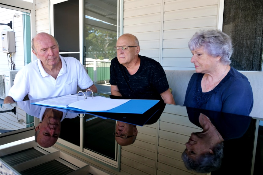 Three older people reading a document