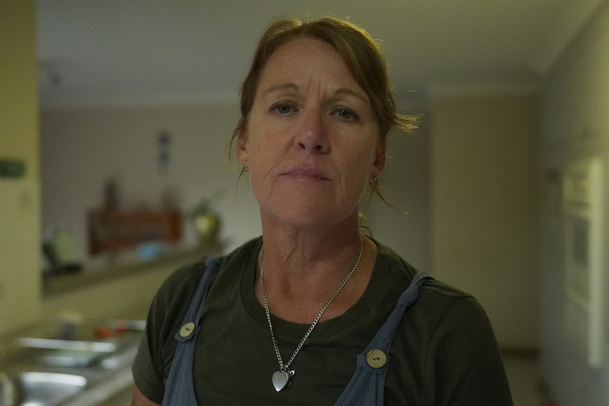 A woman stands in her kitchen, with a serious expression on her face.