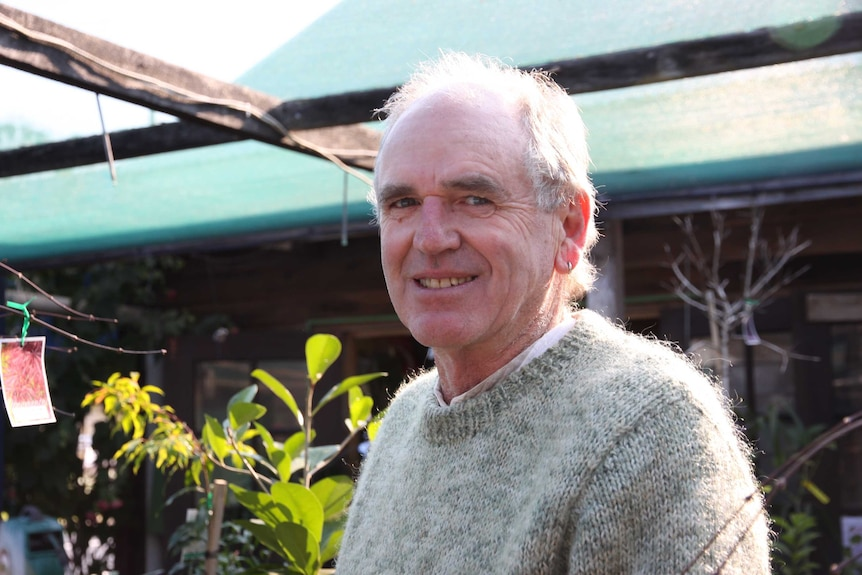 Portrait of a man from mid-torso up, standing in a garden nursery.